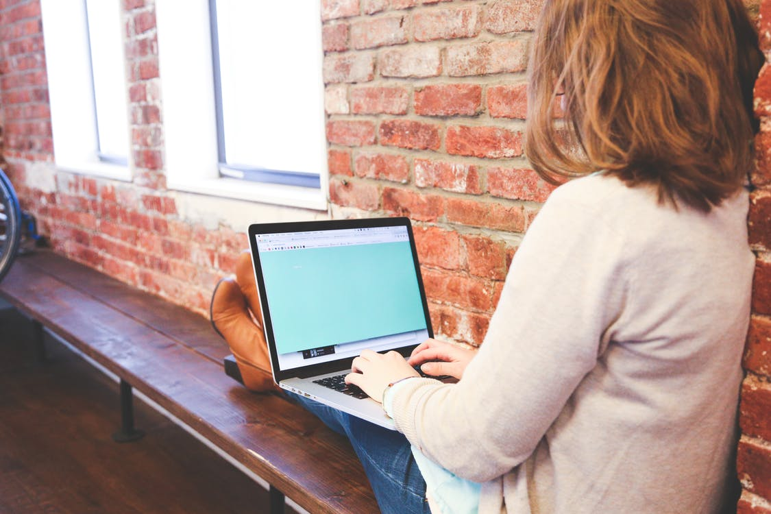 Woman Using Macbook While Sitting on Brown Wooden Bench