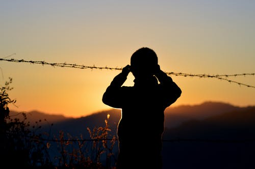 Silhouette of Boy Standing Near Barbed Wire