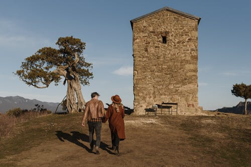 Faceless stylish couple walking towards ancient tower in picturesque nature