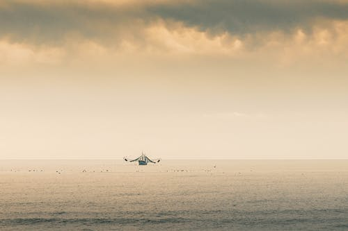 Silhouette of Boat on Sea Under Cloudy Sky