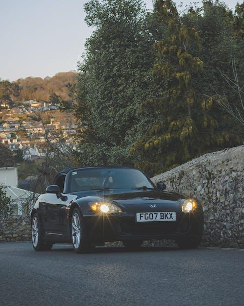 Black Porsche 911 Parked on Gray Rock