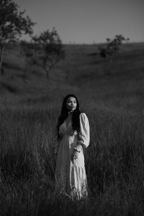 Woman in White Dress Standing on Grass Field in Grayscale Photography