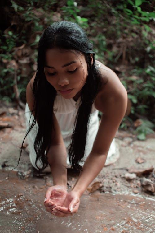 Woman in White Tank Top Sitting on Brown Soil