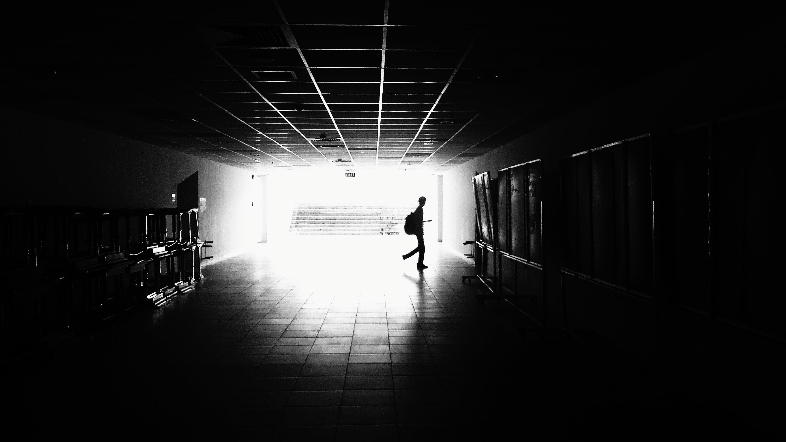 Silhouette of Man Walking on Hall