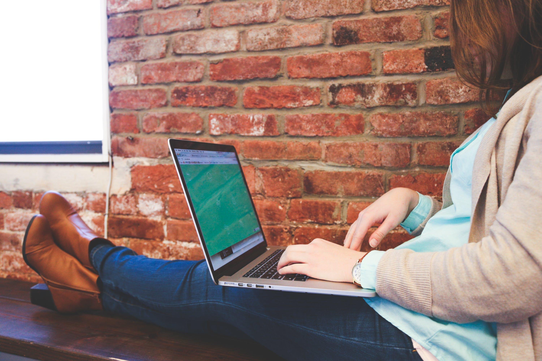 Woman Sitting on Bench Using Macbook