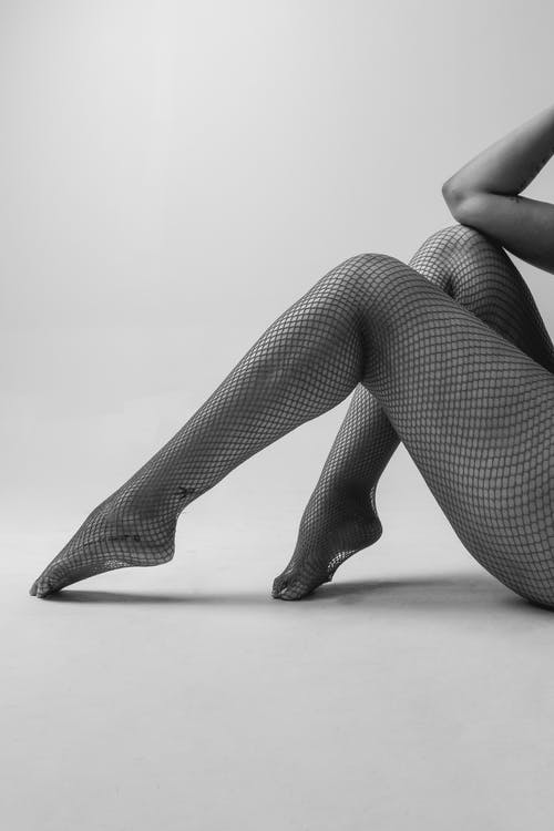 Side view of crop black and white unrecognizable sensual female in fishnet tights sitting on floor in white studio
