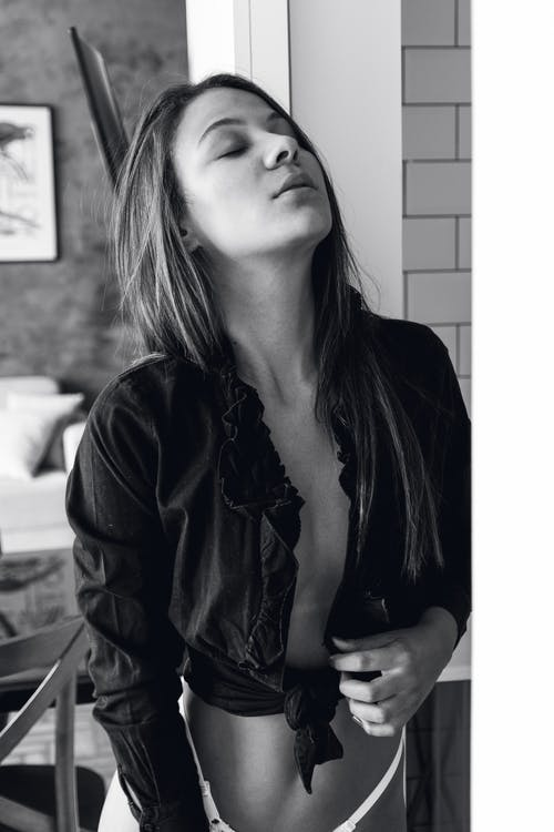 Black and white of pensive young fit lady in stylish shirt on naked body and panties standing in room with closed eyes