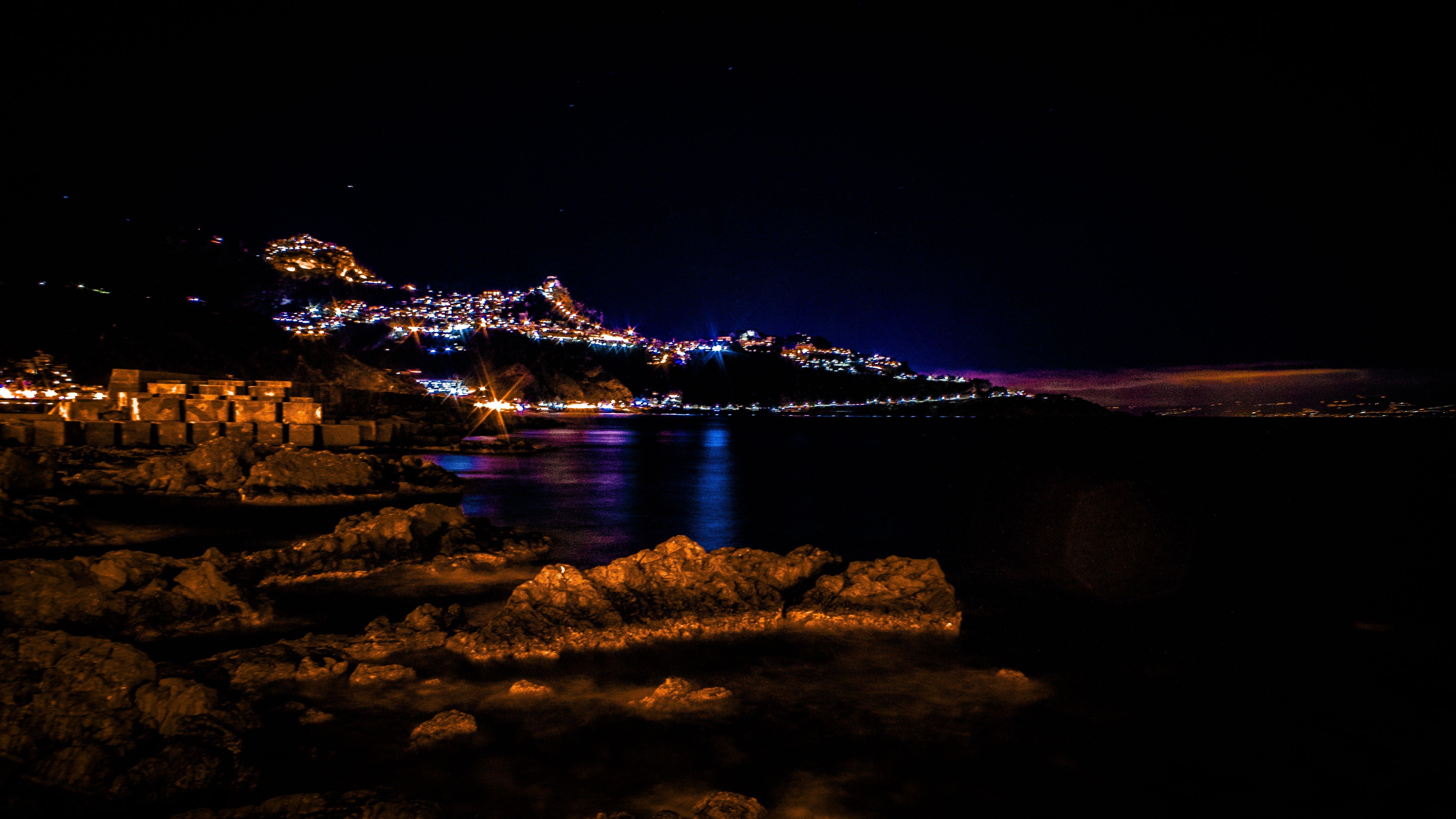 akşam, aydınlatılmış, deniz, deniz kıyısı içeren Ücretsiz stok fotoğraf