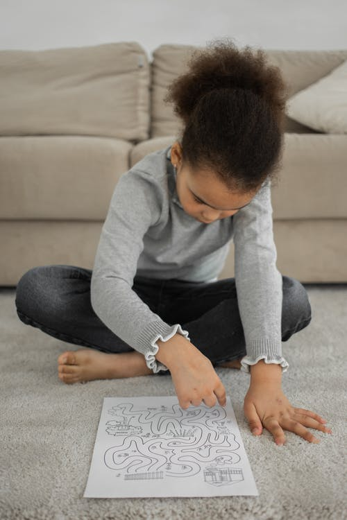 Focused ethnic kid solving printed labyrinth on paper
