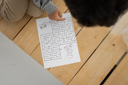 Unrecognizable child solving labyrinth test printed on paper at home