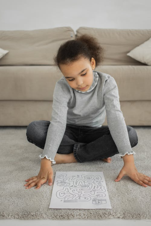 Full body of attentive little ethnic child with dark Afro hair in casual clothes solving maze task while sitting on soft carpet at home