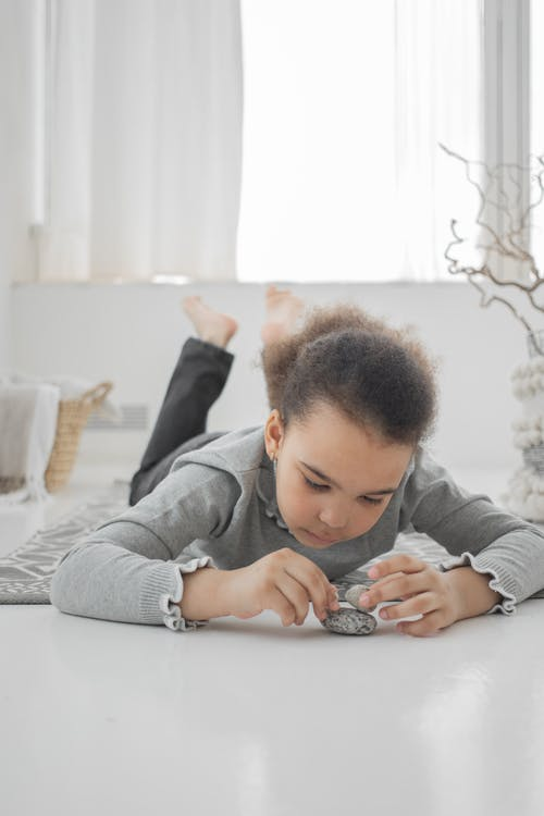 Boy in Gray Long Sleeve Shirt Sitting on White Bed