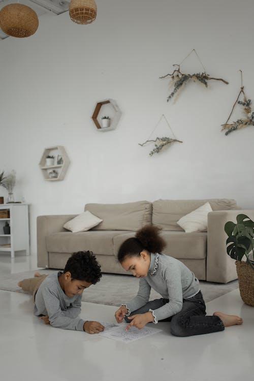 Woman in Gray Jacket Sitting Beside Boy in Gray Sweater