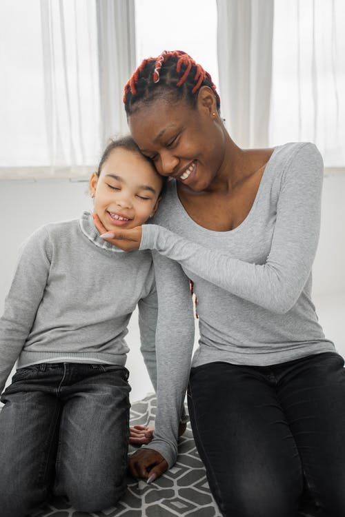 Positive young black woman with Afro braids in casual clothes smiling and touching face of adorable little daughter while sitting together on floor