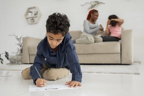 Boy in Blue Dress Shirt Writing on White Paper