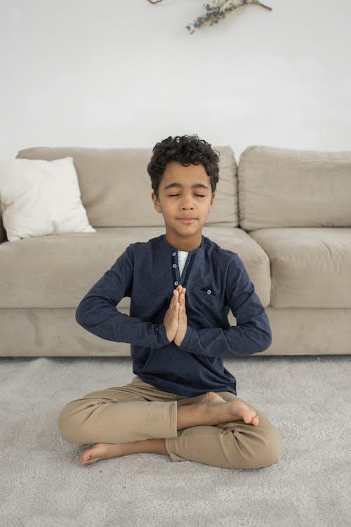 Mindful black boy meditating in room