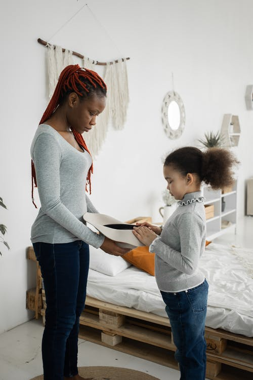 Black woman with hat playing with daughter