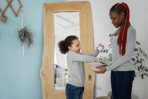 Side view of positive black daughter pulling balls of headdress while playing with African American mother in room with mirror