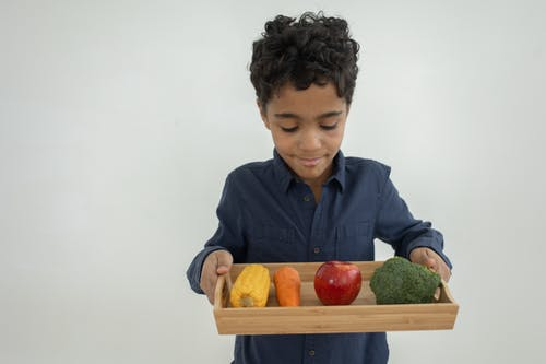 Happy ethnic kid holding wooden tray with colorful raw products