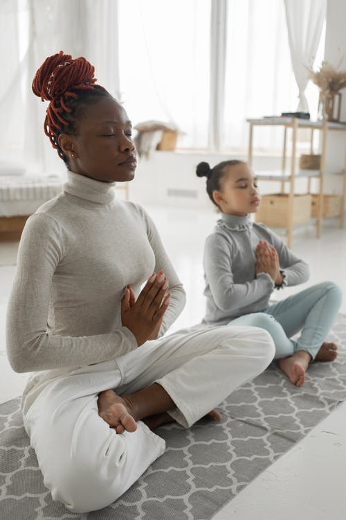 Full body of tranquil young barefooted African American woman in casual clothes sitting on carpet in Padmasana pose with closed eyes while meditating with adorable little daughter at home