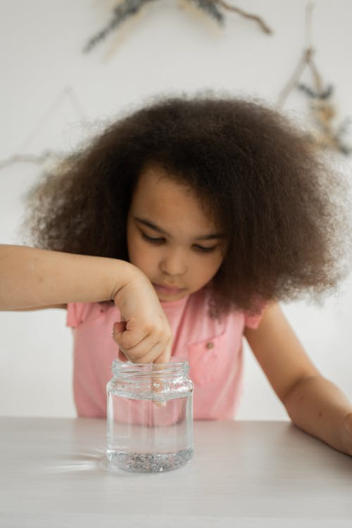 Curious African American child dipping finger into water