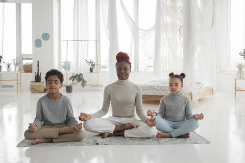 Positive black mother with kids meditating together with closed eyes at home