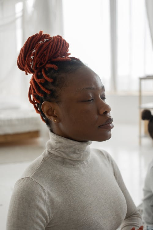Peaceful young African American female in turtleneck with dreadlocks meditating with closed eyes in light bedroom at home