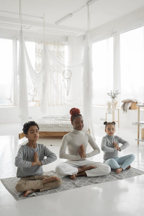 Young ethnic mother with cute children practicing yoga together at home