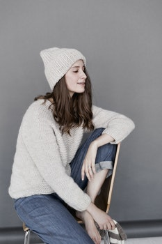 Woman in White Sweater and Beanie With Blue Denim Pants