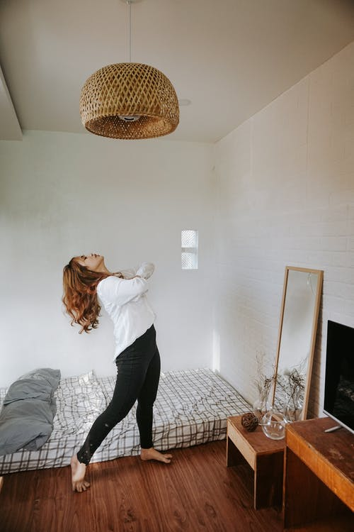 Woman in White Long Sleeve Shirt and Black Pants Standing on Bed