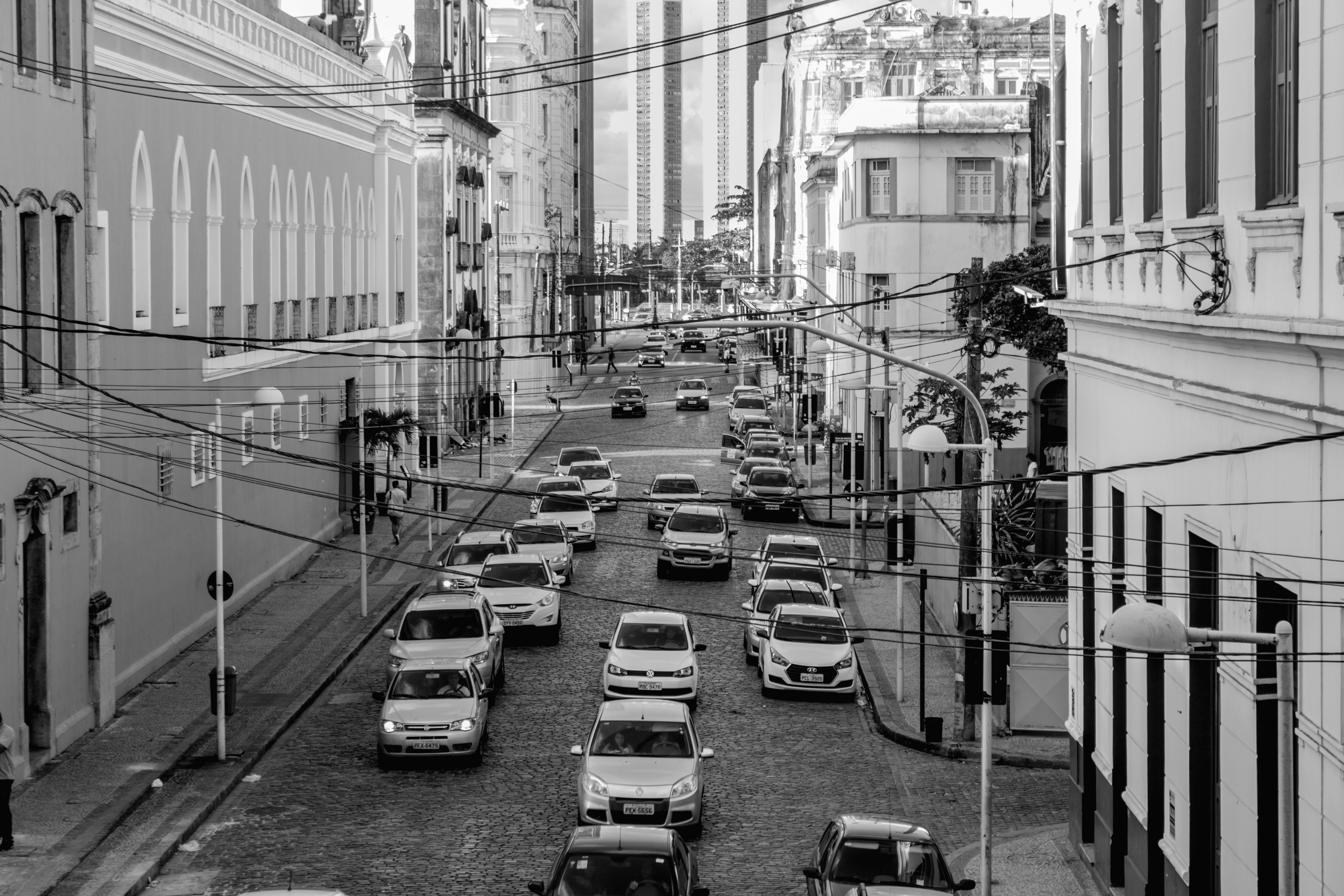 Grayscale Photo of Assorted Cars at the Middle of High Rise Buildings