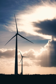 Silhouette Photo of Two Wind Mills during Golden Hour