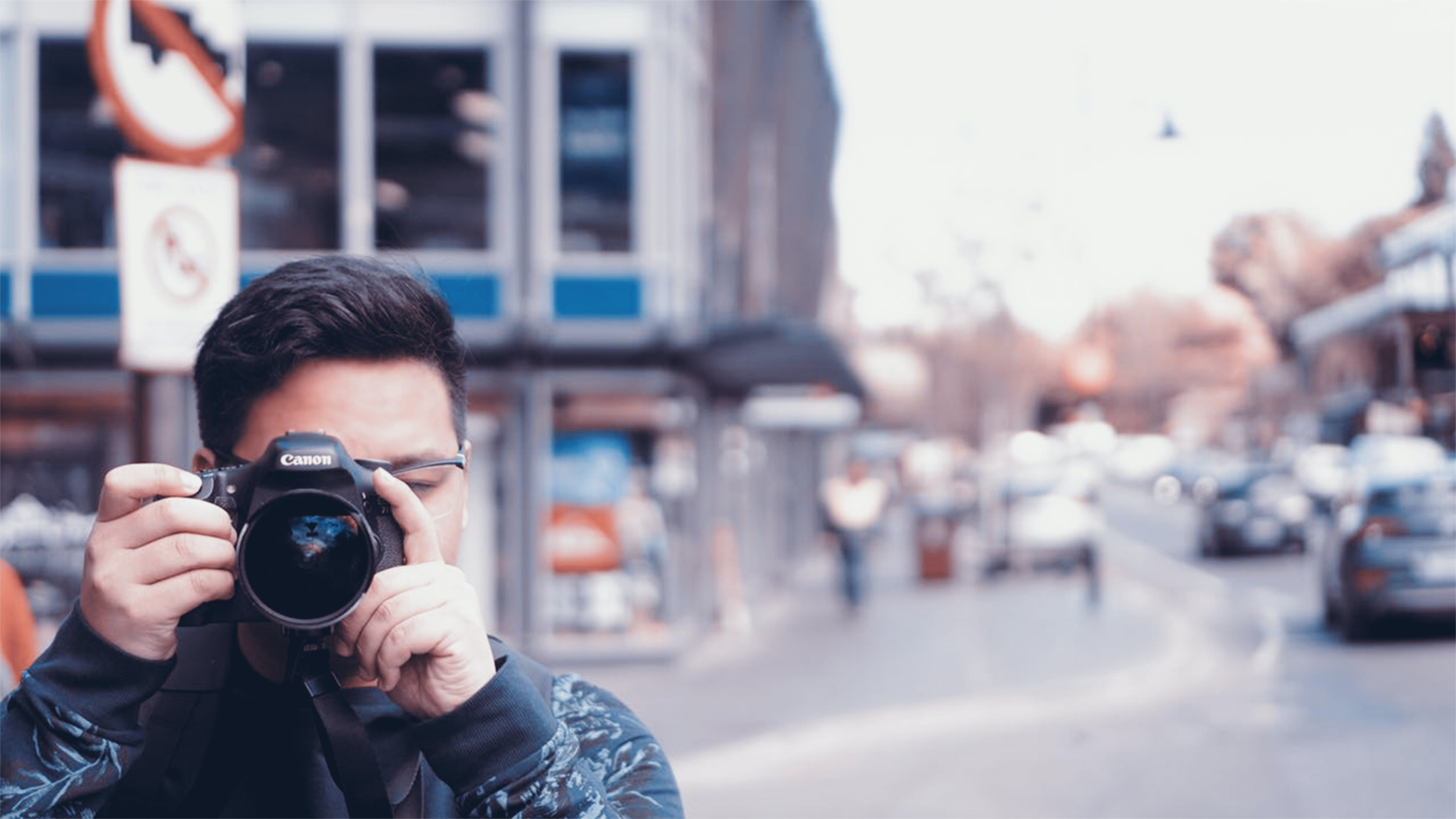 Man Holding A Camera On Busy Street
