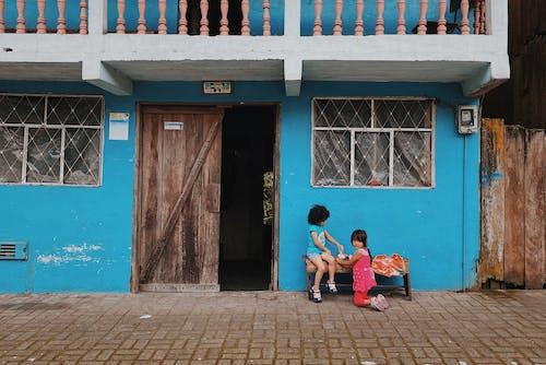2 Women Sitting on Bench Near Door