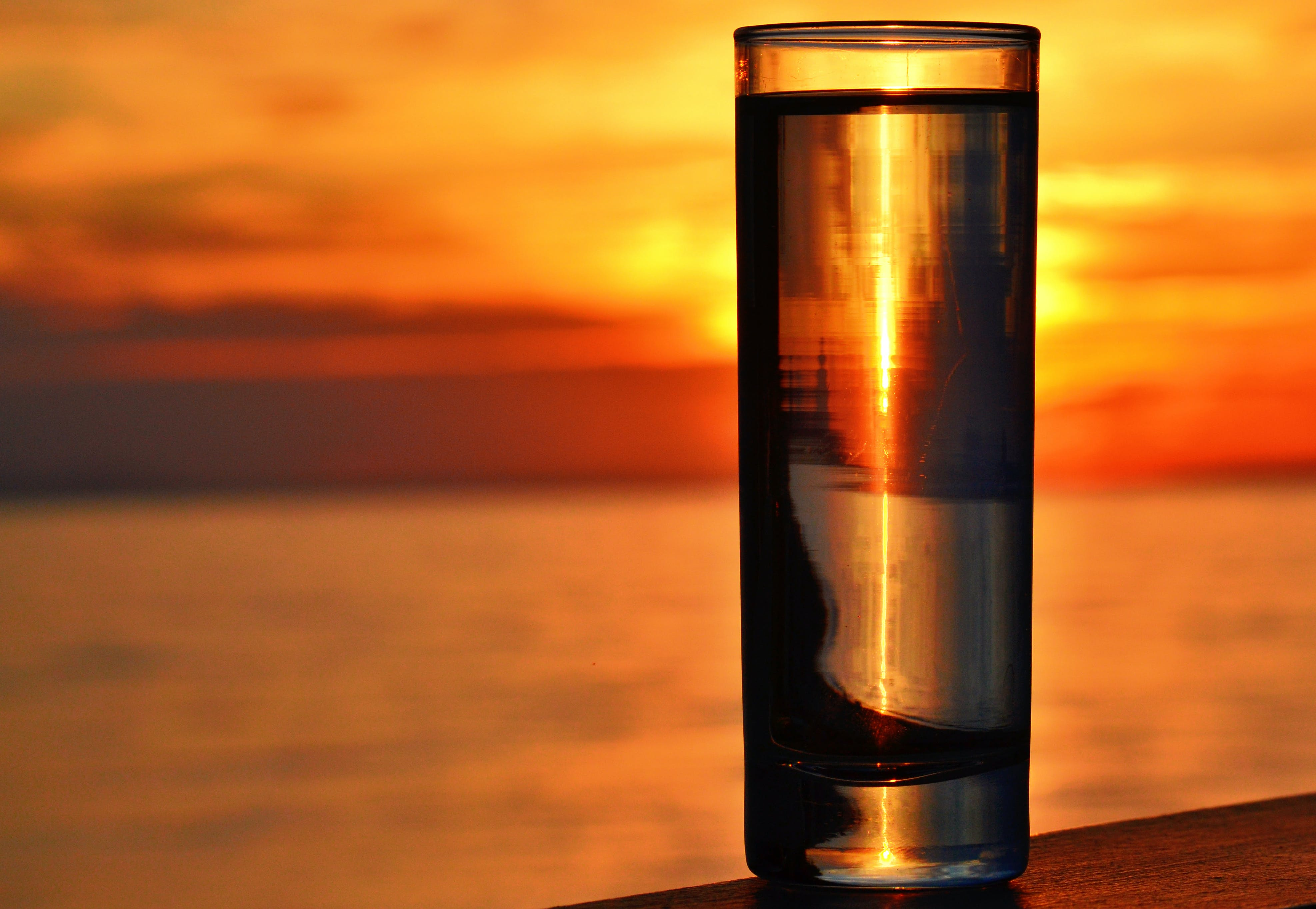 Clear Highball Glass on Brown Surface during Golden Hour