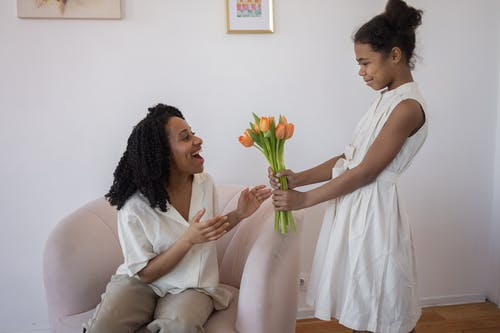A Girl Surprising Her Mother with a Bouquet of Flowers