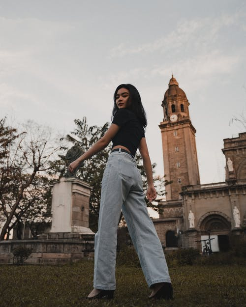 A Girl in Black Shirt and Denim Jeans Standing on Lawn