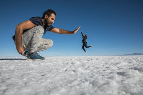 Man in Blue T-shirt and Blue Denim Jeans Jumping on Snow Covered Ground Under Blue