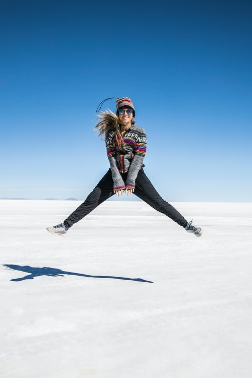 Woman in Black and Red Jacket and Black Pants Standing on Snow Covered Ground