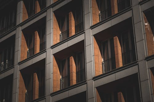 Low angle of symmetric windows windows with French balconies of modern multistory residential building on sunny day in city