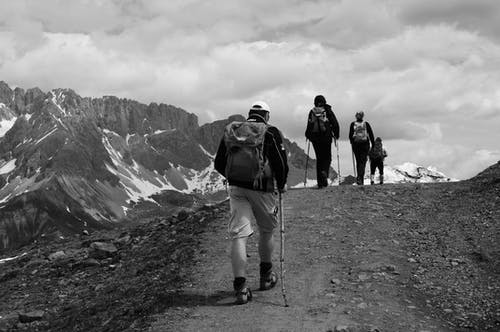 Grayscale Photo of People Hiking on the Mountain