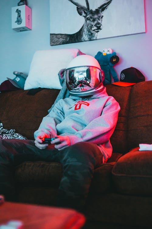 Человек, сидящий на диване в белом шлеме