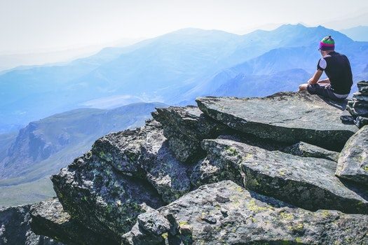 Photography of a Man Sitting on Rock