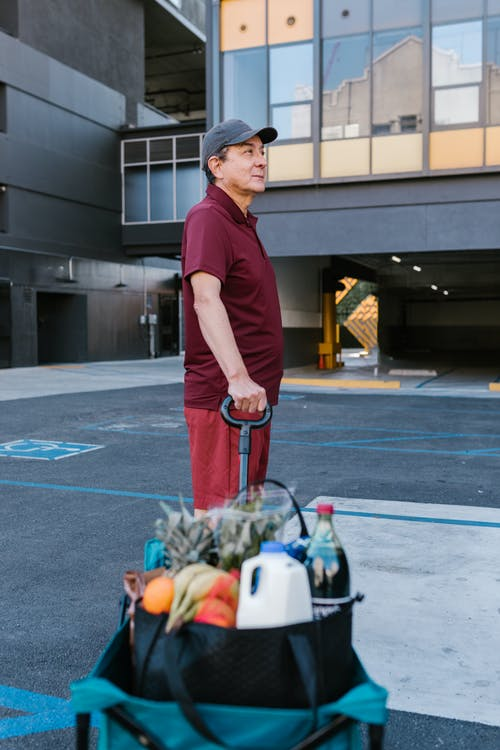 A Man in a Maroon Shirt Holding a Cart of Groceries