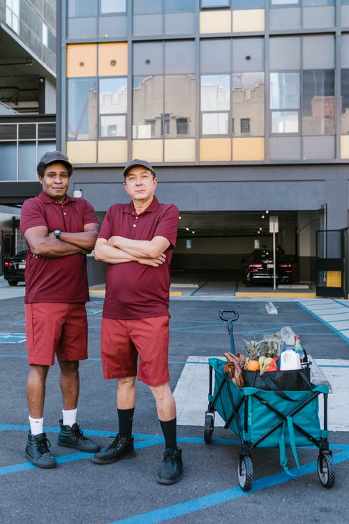 Deliverymen in Maroon Shirts in the Parking Lot