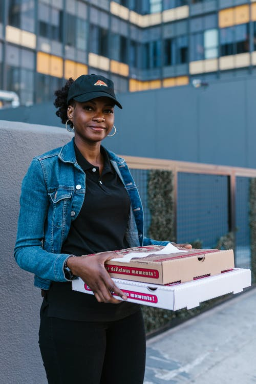 A Woman in Denim Jacket Delivering Pizza