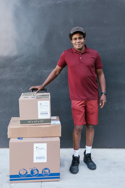 A Man in Maroon Shirt with Packages for Delivery
