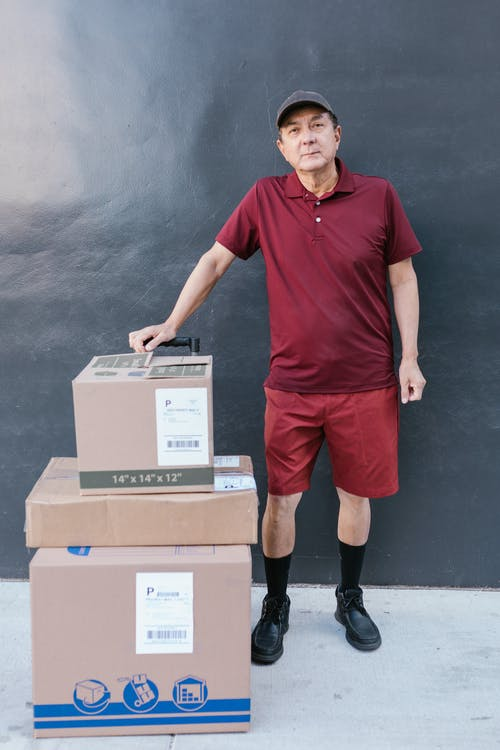 A Elderly Man in Maroon Shirt with Packages for Delivery