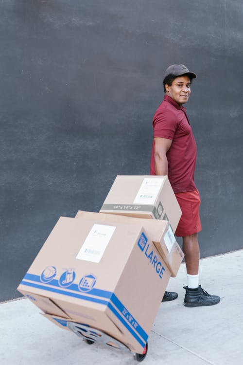 A Man in a Maroon Shirt Delivering Packages