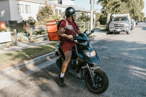 A Deliveryman Riding a Scooter